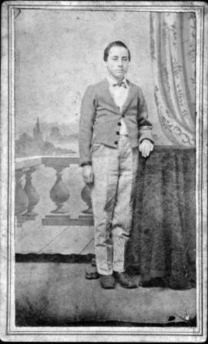 Primary view of object titled '[A young man standing with his left arm resting on a table]'.