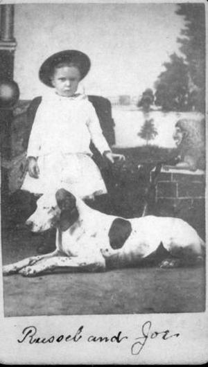 "Primary view of object titled '[A young boy and a black and white dog identified as ""Russel and Joe""]'."