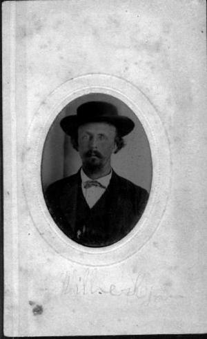 Primary view of object titled '[A man wearing a dark coat, vest, hat, and tie with a white collared shirt]'.