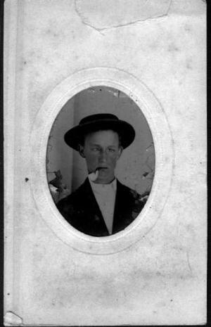 [Bust photograph of a young boy smoking a pipe]