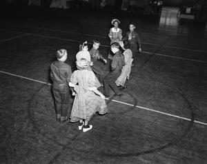 [Eight Children Square Dancing in a Gymnasium]