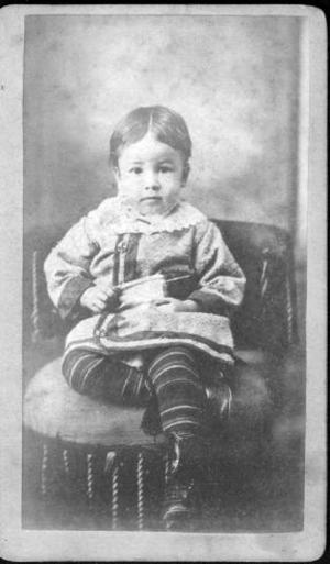 Primary view of object titled '[A young boy sitting in a chair with his legs crossed]'.
