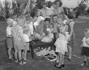 [Children Standing Around a Birthday Cake at a Boy's Birthday Party]
