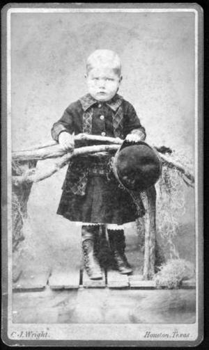 Primary view of object titled '[An unidentified boy standing on a wooden bridge, holding a hat]'.