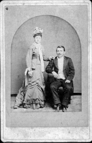 Primary view of object titled '[An unidentified man in a suit and an unidentified woman in a dress and hat]'.