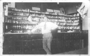 Primary view of object titled '[Arthur Parrott at Pickard and Huggins Drug Store]'.