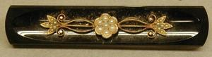 Primary view of object titled '[Black plastic pin with a gold floral design]'.