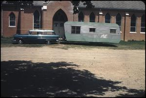 Primary view of object titled '[Car and Trailer Parked Outside Ebeneezer Church]'.