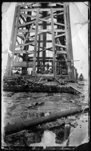 Primary view of object titled '[Wooden oil derrick with oil spurting from the well below]'.