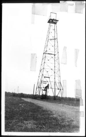 Primary view of object titled '[Metal derrick platform with an oil pump below it]'.