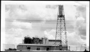 Primary view of object titled '[An oil derrick and a tin building with three storage tanks on top]'.