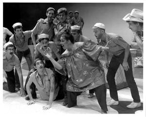 Primary view of [Bloody Mary Shows an Item to the Sailors in South Pacific Musical]