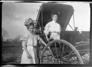 Primary view of [Photograph of Two Women in Hats with Covered Buggy]