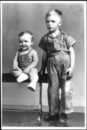Primary view of object titled '[A boy and a toddler sitting on a table]'.