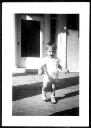 Primary view of object titled '[A toddler walking across a cement patio]'.