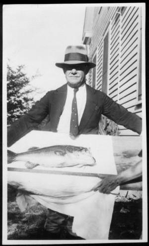 Primary view of object titled '[A man showing off a fish]'.
