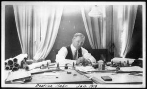 Primary view of object titled '[A man working at a desk]'.