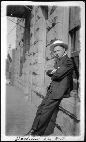 Primary view of object titled '[A man leaning against a window sill of a building with his arms folded]'.