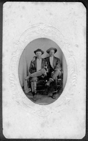 [Two unidentified men sitting in wooden chairs with their legs crossed]