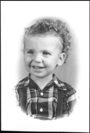 Primary view of object titled '[A child with short curly hair, wearing a plaid shirt and suspenders]'.