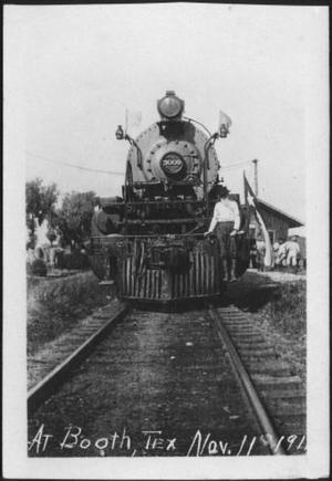 [Postcard image of a man standing on the front of a locomotive]