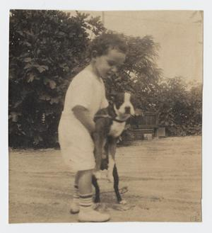 Primary view of object titled '[Photograph of Child Standing While Holding a Dog]'.