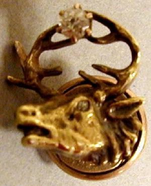 Primary view of object titled '[Gold pin in the shape of wild game with large antlers, antlers are holding a diamond]'.