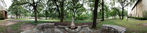 Panoramic image of a statue and seating area outside the Little Chapel in the Woods.