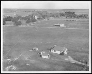 Primary view of object titled '[Aerial photograph of a house and small buildings on the George Ranch site]'.