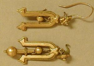 Primary view of object titled '[One of a pair of horseshoe shaped gold dangle earrings]'.