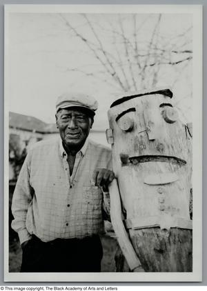 Black and white photograph of John Lewis Hunter standing outdoors next to a large wooden sculpture of a human figure.