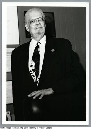 Black and white photograph of Fred L. Lander III standing behind a chair.