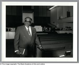 Black and white photograph of Rev. Foster standing in a large church next to a pew. He holds a book in one hand.