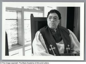 Black and white photograph of Dr. Sylvester Marilyn Wright, seated and wearing white robes with a black sash with crosses at his chest.