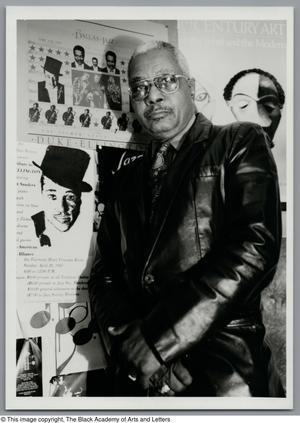 Black and white photograph of Allison Tucker standing in front of a large poster with text and images of musicians. He wears a taylored leather jacket.