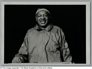 Black and white photograph of James Harrison. He wears a sweatband around his head and a track suit.