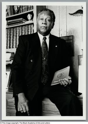 Black and white photograph of Dr. Norman E. Dyer sitting on the edge of a desk. He holds a book in one hand.