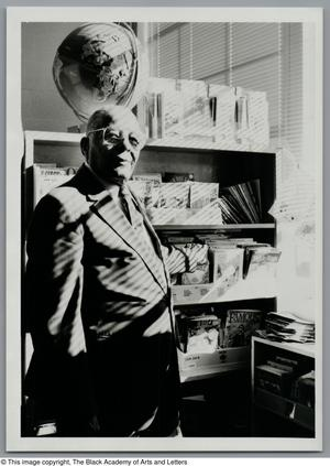Black and white photograph of David Daniels standing in front of a bookcase with a globe on top. Lined shadows from window blinds are cast over him.