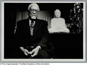 Black and white photograph of Dr. Donald A. Brooks seated, with a white buddhist statue to the right.