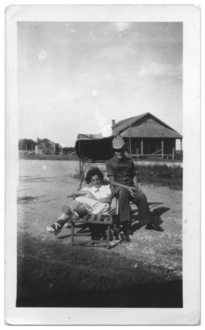 Primary view of object titled '[Young man and woman sitting on an outside chair]'.