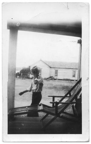 Primary view of object titled '[Man walking by porch]'.