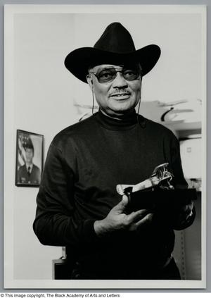 Black and white photograph of Maj. John F. Briggs, wearing a black stetson and holding a small model plane.