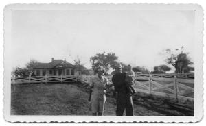 [Unidentified family in front of rural home]