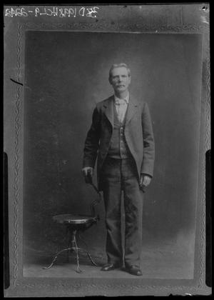 Primary view of object titled '[Portrait of Man in Suit Standing Beside Chair]'.
