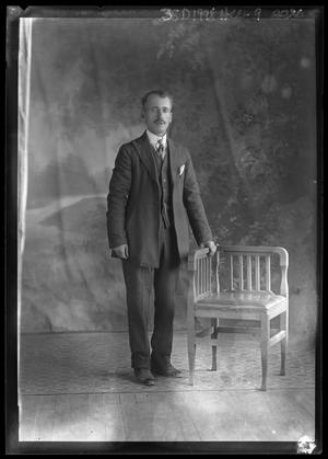 Primary view of object titled '[Portrait of Man Standing Beside Chair]'.