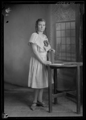 Primary view of object titled '[Portrait of Girl Standing Beside Table]'.