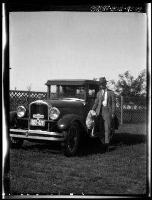 Primary view of object titled '[Portrait of a Man and a Dog Beside an Automobile]'.