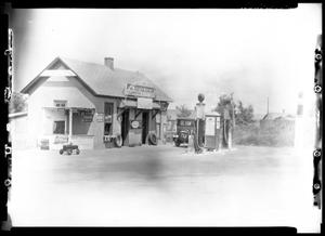Primary view of object titled '[Photograph of a Service Station and an Automobile]'.