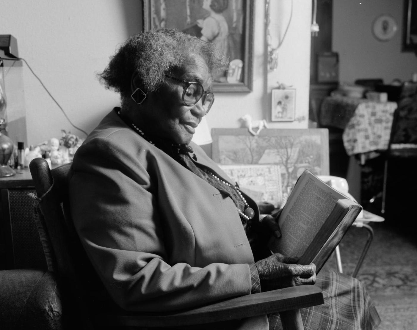 Black and white close up photograph of Osceola Mays seated in a chair looking at a book.
