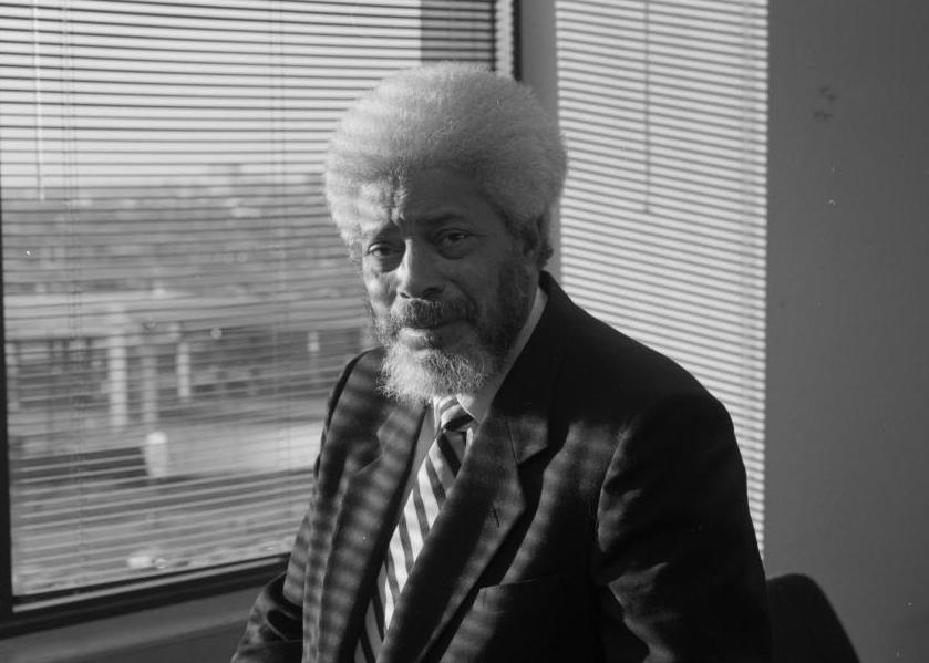 Black and white close up photograph of J.B. Jackson in front of a window.